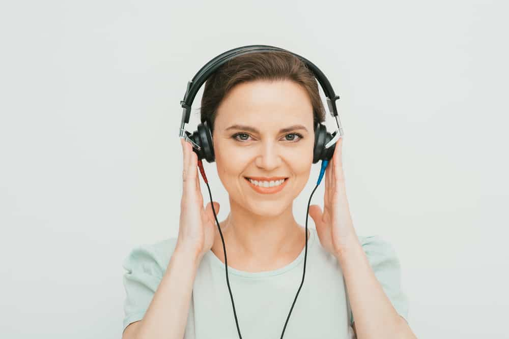 Hearing test, hearing diagnostic. A woman wearing headphones having an audiometry test isolated in white